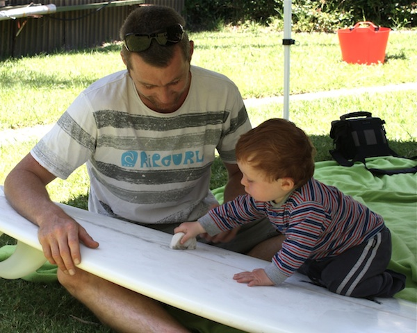Steve passing on the all important wisdom of how to wax a surfboard to Van
