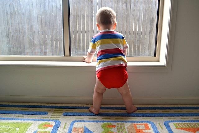 Otis standing at window ledge