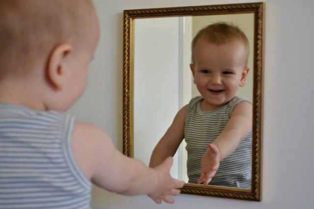 child looking in mirror. looking at reflection care of self area child in mirror b