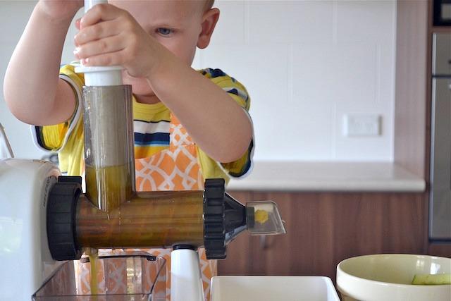 Caspar pushing fruit into juicer