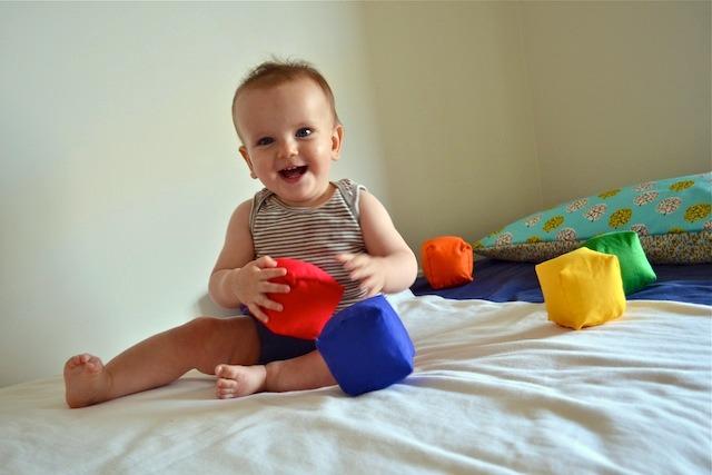 Otis on floor bed playing with handmade soft blocks.
