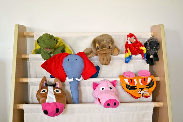 Puppets stored on book shelf.