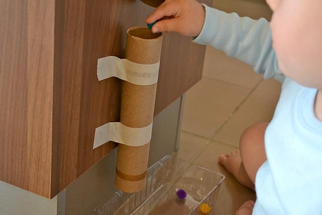 Putting pom-pom into cardboard tube