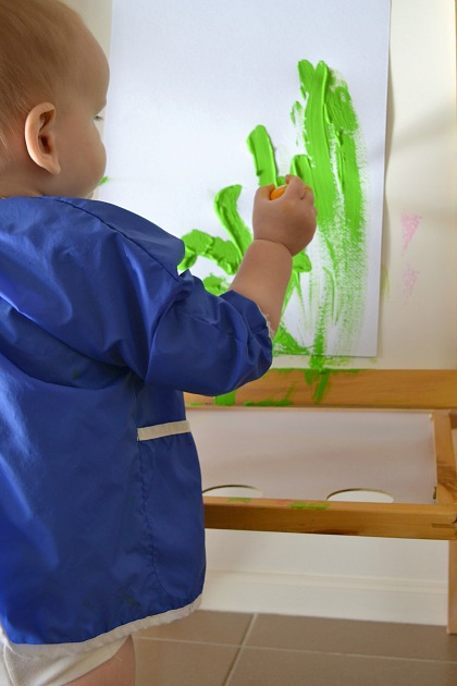 Standing at easel and painting