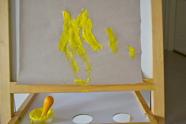 Easel with paper, paint pot and brush