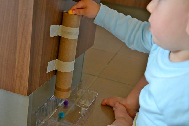 Putting pom pom into cardboard tube