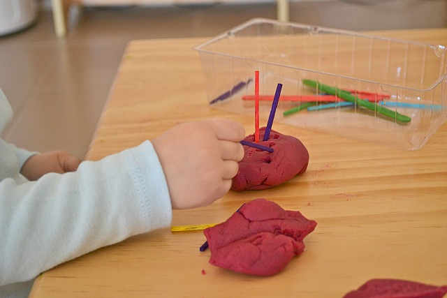 Putting matchsticks into playdough